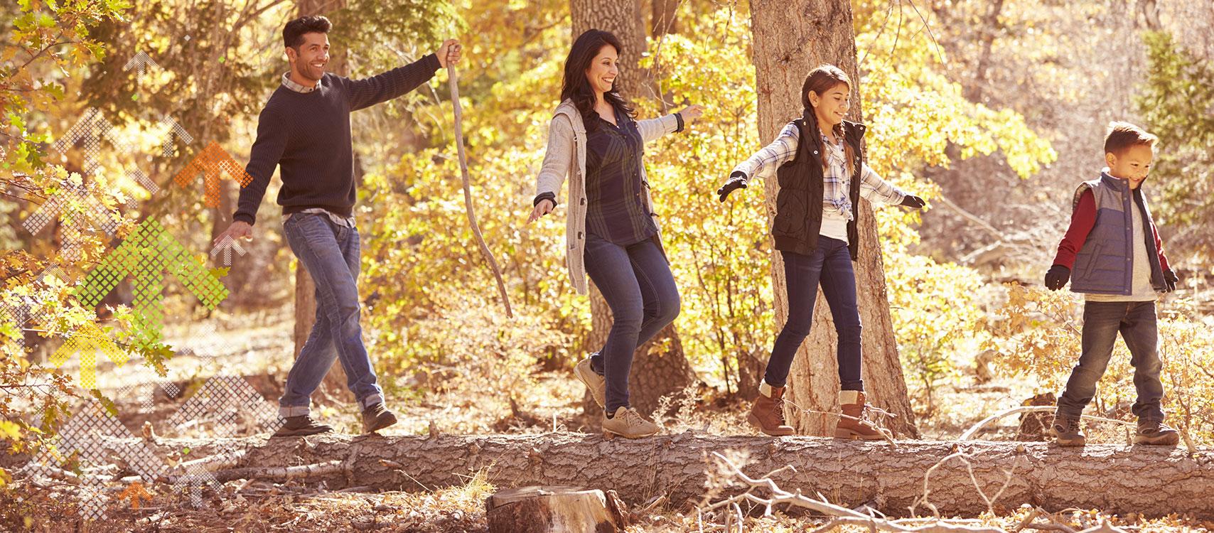 Familie balanciert über Baumstamm im Wald