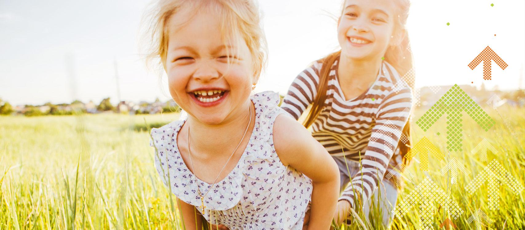 Mädchen rennen lachend über eine Wiese