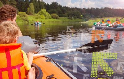 Familie ist mit mehreren Gummiboten auf einem Fluss unterwegs