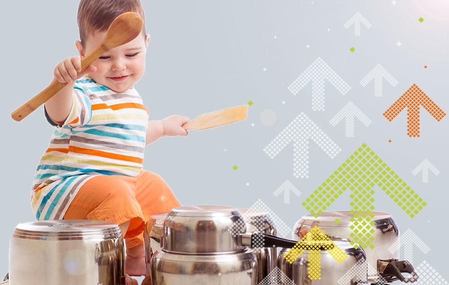 Kind haut mit Holzlöffel auf Pfannen
