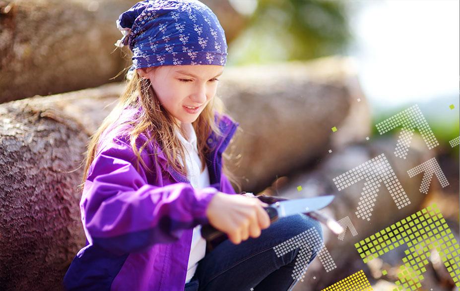Mädchen sitzt auf einem Baumstamm und schnitzt einen Stock mit dem Taschenmesser