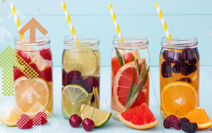 Gläser mit Wasser und verschiedenen Früchten und Kräutern darin.
