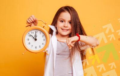 EIn Mädchen Hält eine Uhr in der Hand.