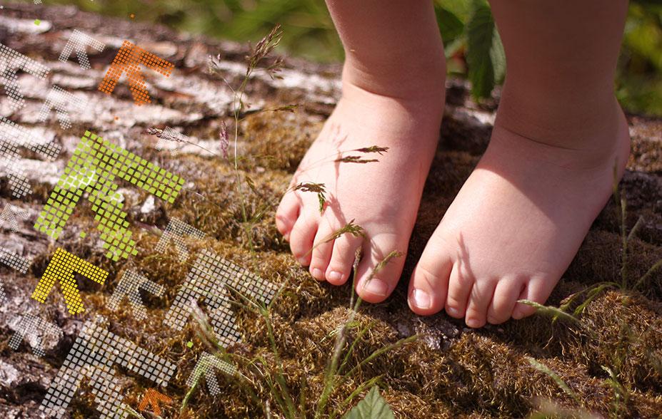Kind läuft mit den Füssen auf einem liegenden Baumstamm