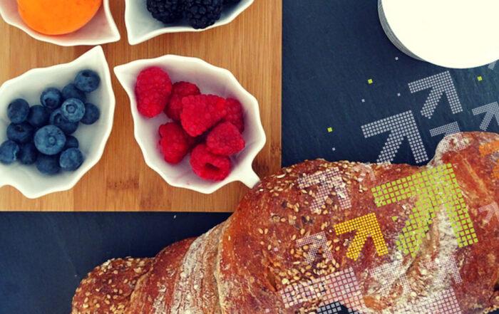 Auf dem Bild sind die Zutaten für die Früchte Bruschatte zu sehen. (Früchte, ein Vollkornaguette und Frischkäse)