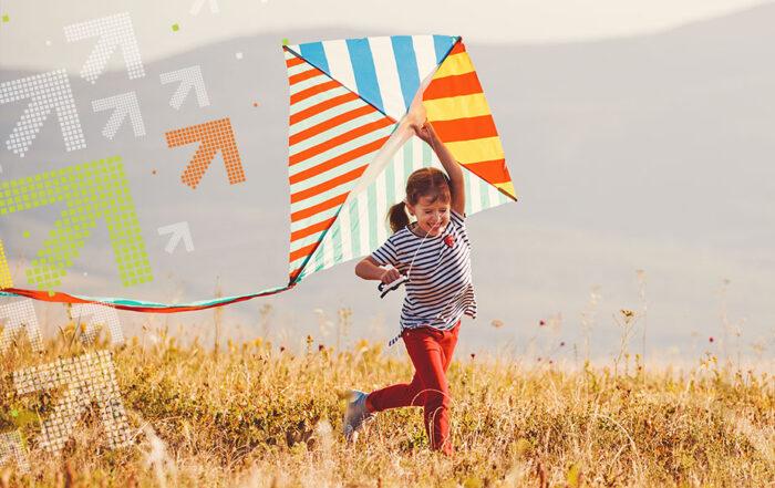 Kind rennt mit Drachen über die Wiese