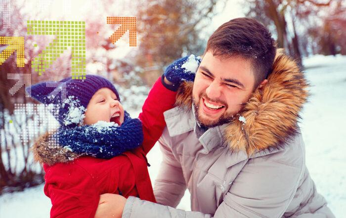 Sohn stopft Vater einen Schneeball in den Kragen.