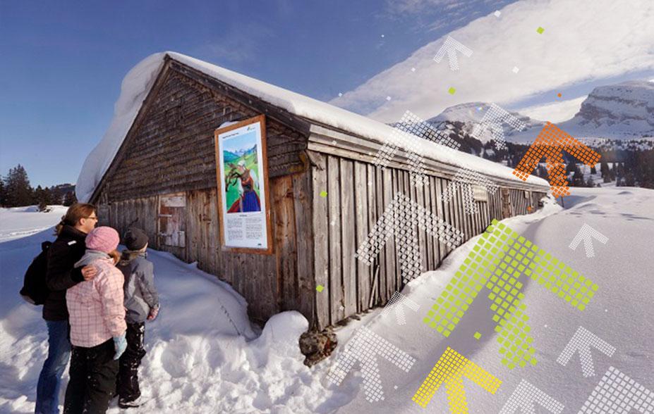 Sagenweg Toggenburg- Frau steht mit zwei Kindern im Schnee vor einer Tafel.