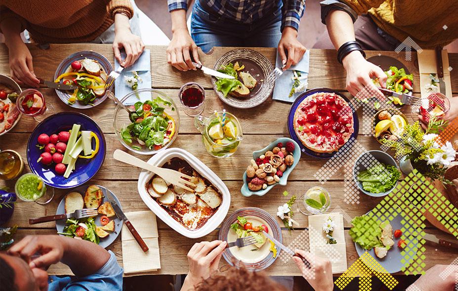 Tisch mit vielen verschiedenen Speisen und eine Familie, die am essen ist - Top 5 Rezepte für Familien
