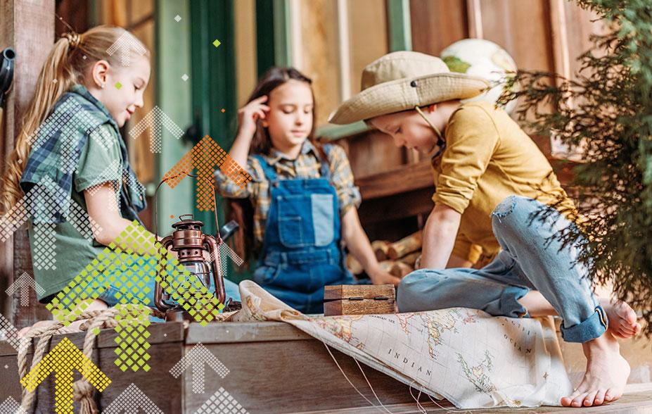 Kinder Sitzen auf dem Boden und suchen auf der Karten einen Schatz. Geocaching